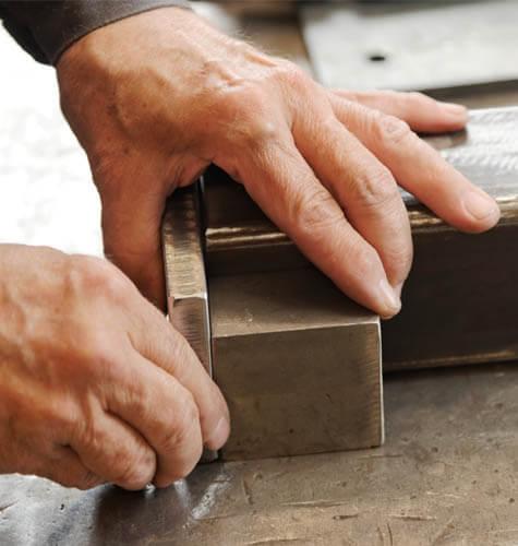 Zámočnícke práce, napríklad lisovanie, zváranie alebo strihanie plechov.